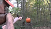 This man carves his pumpkin using his rifle