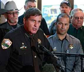 Weld County, Colo., Sheriff John Cooke, left, with El Paso County Sheriff Terry Maketa, center right, and other sheriffs standing behind him, speaks during a news conference at which he announced that 54 Colorado sheriffs are filing a federal civil lawsuit against two gun control bills passed by the Colorado Legislature. (AP Image)