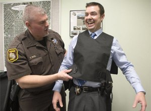 Corrections Officer Dave Bohl, left, straps a stun vest onto Saginaw County Sheriff William Federspiel, April 4, 2014. The department bought the vest to control unruly inmates during transport or defendants who are causing trouble in court. The vest delivers electric shocks to the back of the person wearing it and can fit under clothing so it is not visible. (Image Jeff Schrier/MLive.com)