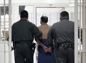 An inmate, on suicide watch, is escorted by correctional officers at the California Substance Abuse Treatment Facility in Corcoran, Calif. (AP Photo/Rich Pedroncelli, File)