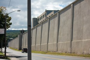 The Clinton Correctional Facility perimeter wall dominates the streetscape. The tailor shop building where the convicts worked can be seen in the background. (Photo by Charles A. Gardner)