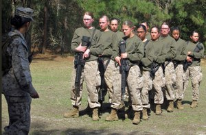 In this Feb. 21, 2013 file photo, female recruits stand at the Marine Corps Training Depot on Parris Island, S.C. New physical standards established so women can compete for combat posts in the Marine Corps have weeded out many of the female hopefuls. But data obtained by The Associated Press shows they're also disqualifying some men. (AP Photo/Bruce Smith, File)
