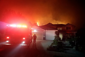 A firefighter walks next to an engine as crews make a stand in front of an advancing wildfire in a residential neighborhood Friday, Nov. 9, 2018, in West Hills, Calif. (AP Photo/Marcio Jose Sanchez)