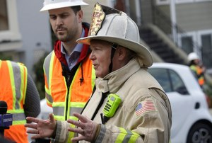 San Francisco fire chief Joanne Hayes-White gestures in front of Pacific Gas and Electric spokesperson Paul Doherty while speaking to reporters about a fire on Geary Boulevard in San Francisco, Wednesday, Feb. 6, 2019. (AP Photo/Jeff Chiu)