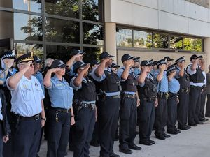 Officers salute the colors during a 9/11 memorial flag raising ceremony. (image/GovX)