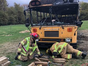 Two Lee's Summit firefighters examine a burned school bus.
