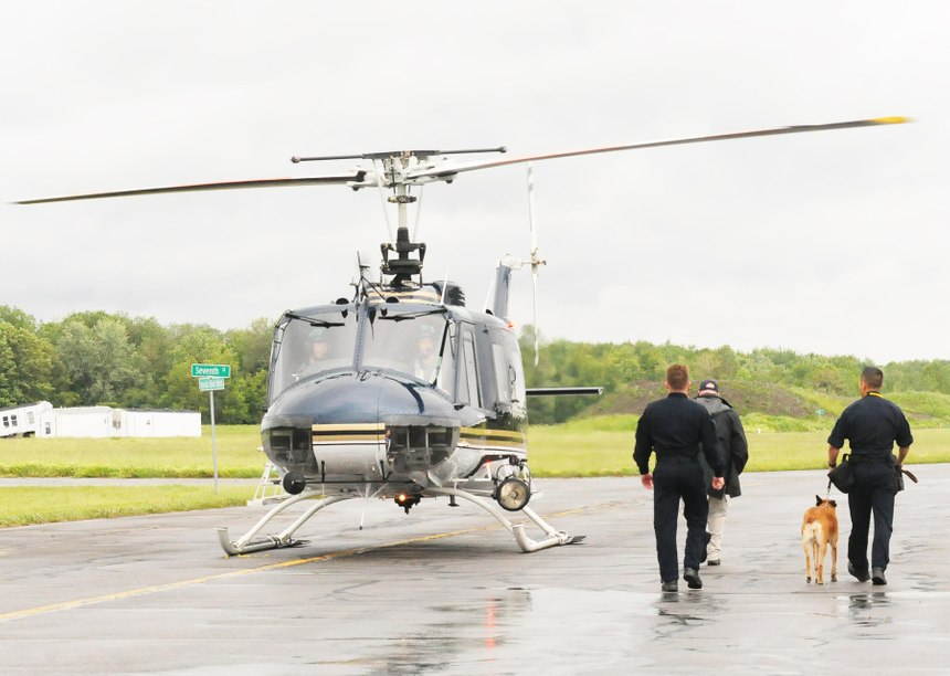 Law enforcement officers escort a police canine to a helicopter for a training exercise that will familiarize canines with the experience of being airborne onJune 13, 2019at the State Preparedness Training Center in Oriskany. [JOLENE CLEAVER / OBSERVER-DISPATCH]