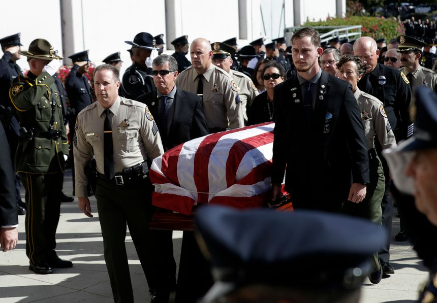 A casket with the body of Ventura County Sheriff's Sgt. Ron Helus is carried into the Calvary Community Church Thursday, Nov. 15, 2018. (AP Photo/Marcio Jose Sanchez, Pool)