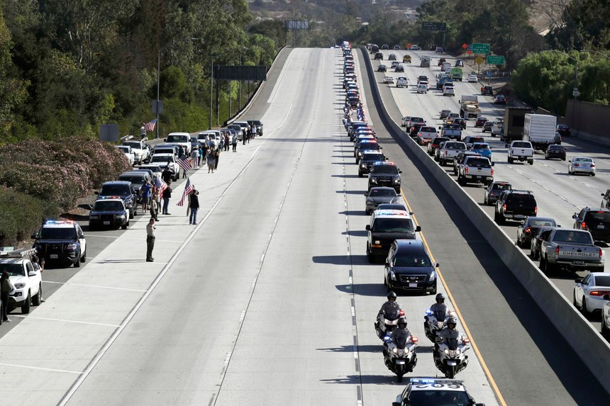 A law enforcement motorcade, providing an escort for a hearse carrying the body of Sgt. Ron Helus, makes its way northbound on Highway 101 Thursday, Nov. 8, 2018, in Newbury Park, Calif. Helus was fatally shot while responding to a mass shooting at a country music bar in Southern California. (AP Photo/Marcio Jose Sanchez)