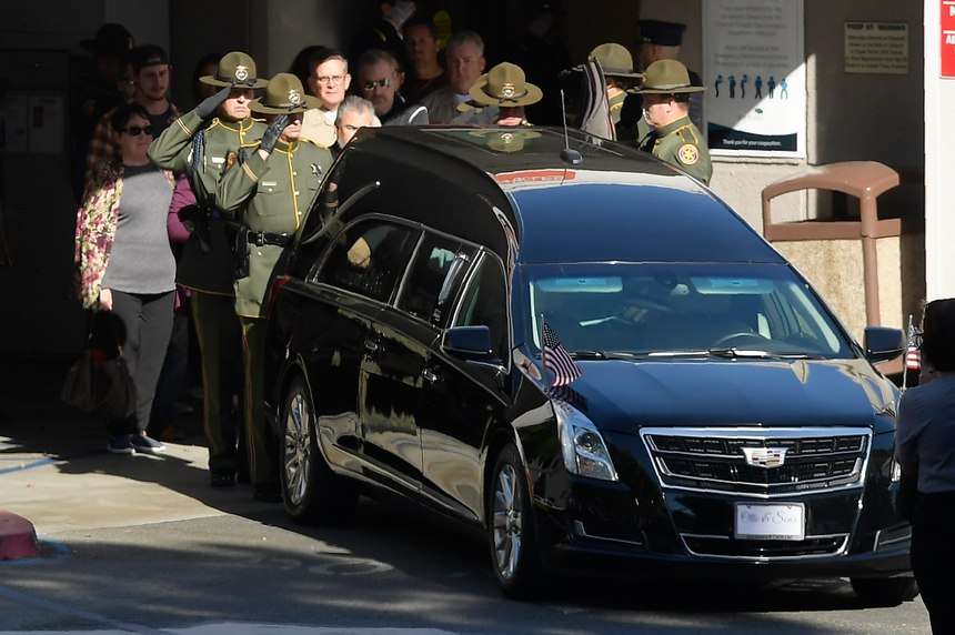 An honor guard salutes the body of Sgt. Ron Helus before it departs the Los Robles Regional Medical Center Thursday, Nov. 8, 2018, in Thousand Oaks, Calif. Helus was killed after a gunman opened fire the night before inside a country dance bar crowded with hundreds of people. (AP Photo/Mark J. Terrill)