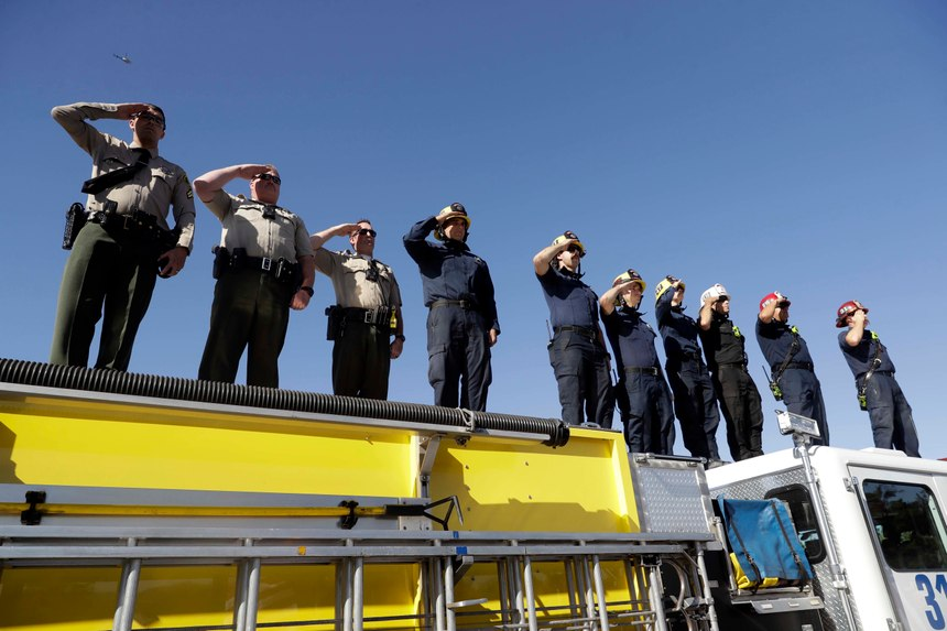 Law enforcement and fire personnel salute from an overpass as a motorcade with the body of Sgt. Ron Helus passes by Thursday, Nov. 8, 2018, in Newbury Park, Calif. Helus was fatally shot while responding to a mass shooting at a country music bar in Southern California. (AP Photo/Marcio Jose Sanchez)