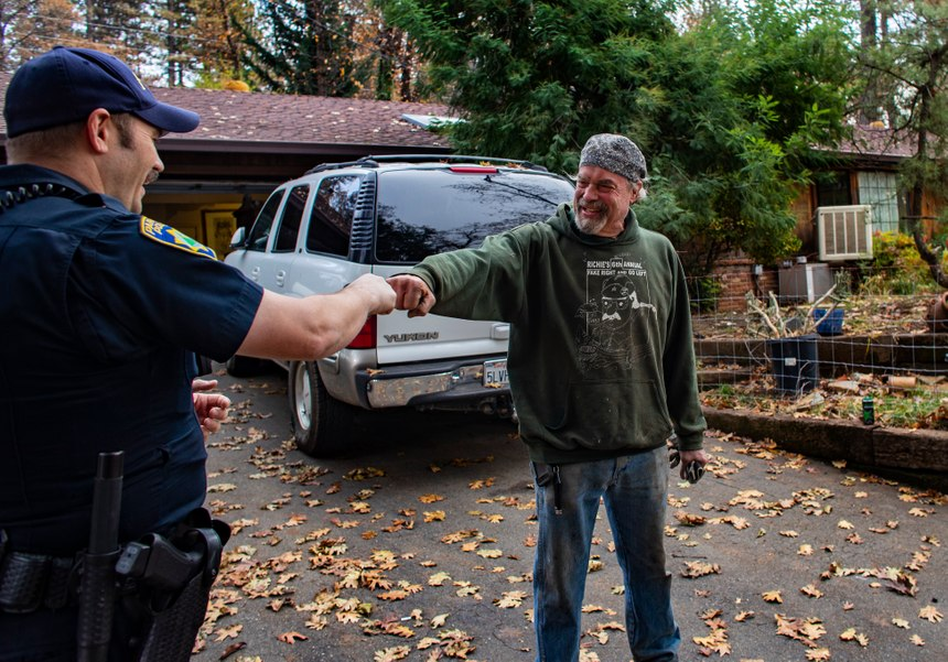 Paradise Police Officer Perry Walters checks on the welfare of resident Brad Weldon, who refused to leave his property during the fire, on Nov. 26, 2018 in Paradise, Calif. Weldon is grateful that the police bring him and his 90-year-old mother supplies, but he questions why he isn't allowed to leave to get supplies himself and return. Once he leaves, he won't be allowed back. Most of the homes around Weldon's burned to the ground, though Weldon's was unscathed. (Gina Ferazzi/Los AngelesTimes/TNS)