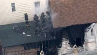 Firefighter falls through roof of burning home