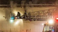 Fire engulfs aerial ladder with firefighter on tip