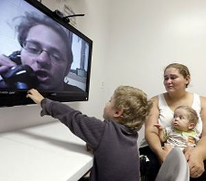 In this photo taken on Tuesday, May 5, 2015, inmate Jesse Cole is shown on a television screen as his son William, 4, center, reaches to touch the screen while his mother, Edna, holds 8-month-old Jesse James, during a video visitation with at the Fort Bend County Jail, in Richmond, Texas. (AP Photo/David J. Phillip)