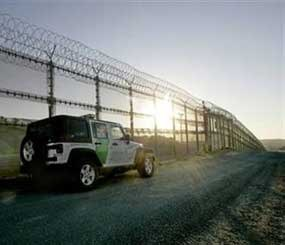 """A U.S. Border Patrol vehicle guards the border fence with its concertino wire topping in San Diego. The """"virtual border fence"""" will be used to compliment some physical fencing already in place, and in some cases, there will be no visible fencing at all. (AP Photo)"""